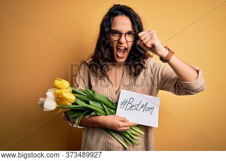 Young beautiful mom with curly hair holding flowers and card as mothers day present annoyed and frustrated shouting with anger, crazy and yelling with raised hand, anger concept