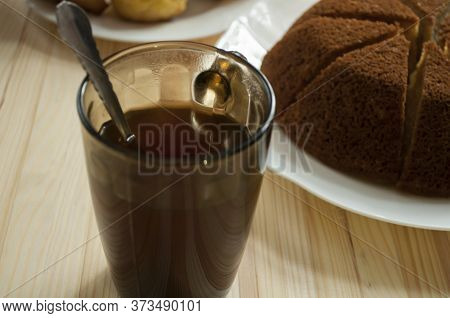 Pie Cut Into Pieces And A Cup Of Tea On A Wooden Background. Pie On A  White Plate. A Cup In The For