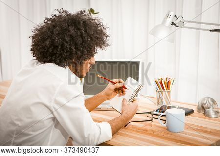 Side View Of Shaggy Man Making Notes In His Paper Notebook Or Scratchpad Sitting At Wooden Table Wit