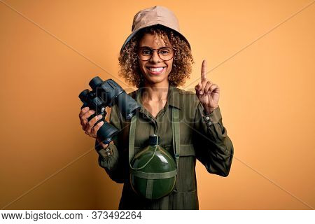 African american tourist woman wearing explorer hat and water canteen holding binoculars surprised with an idea or question pointing finger with happy face, number one