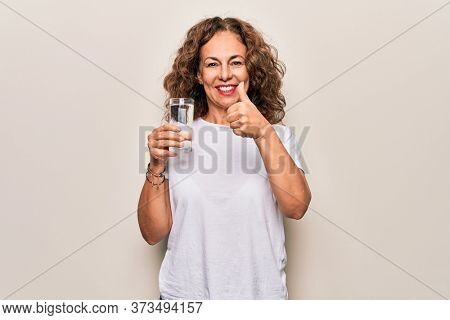 Middle age beautiful woman drinking glass of water to refreshment over white background smiling happy and positive, thumb up doing excellent and approval sign