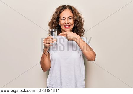 Middle age beautiful woman drinking glass of water to refreshment over white background smiling happy pointing with hand and finger