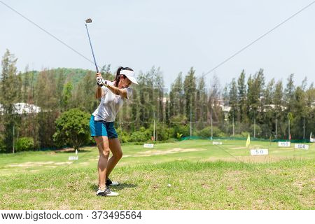 Healthy Sport.  Asian Sporty Woman Swing Golf Ball Practice At Golf Driving Range On Evening On Time