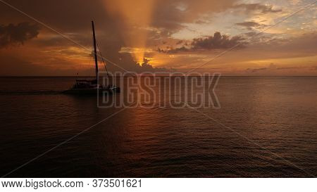 A Boat Slowly Sailing In The Calm Ocean Enjoying A Beautiful Sunset