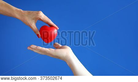 Female Hand Passes Red Heart To Male Hand Against Blue Background Closeup. Kindness And Charity Conc