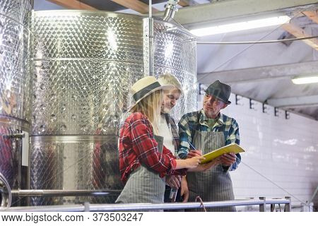 Winemaker and team with checklist for quality control in the winery