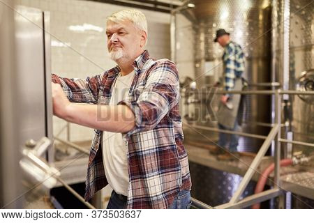 Master brewer or winemaker controls the production at the fermentation tank