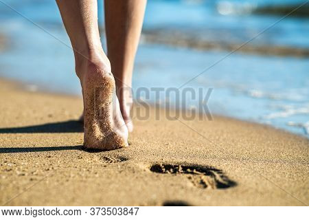 Close Up Of Woman Feet Walking Barefoot On Sand Leaving Footprints On Golden Beach. Vacation, Travel