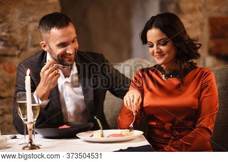 Romance and dating concept. Young couple man and woman celebrating and eating delicious dessert in restaurant. Two people male and female in elegant evening suit and dress on romantic dinner.