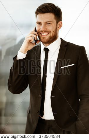 Business concept. Happy smiling young businessman standing in office talking on a cell phone getting good news about his work. Man in suit indoors on glass window background.
