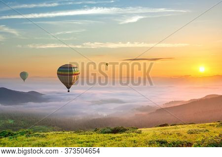 Big Hot Air Baloons Over Idyllic Landscape With Green Grass Covered Morning Mountains With Distant P