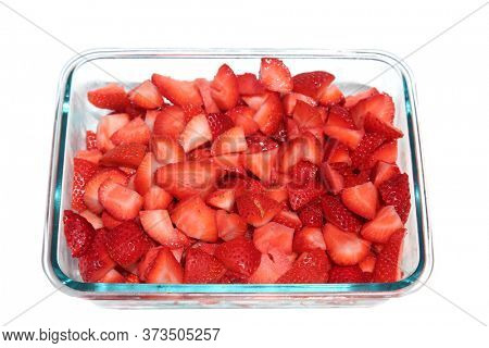 Strawberries. Cut and cubed Strawberries in a glass bowl. Isolated on white. Room for text.