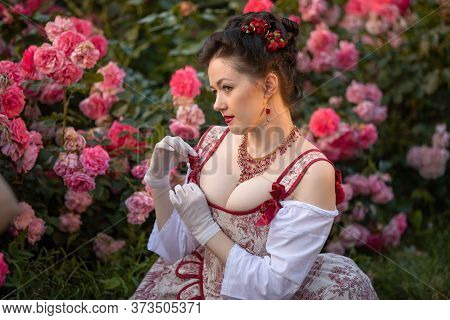 Woman Bride In A Ancient Vintage Historical Dress Posing In The Beautiful Summer Rose Garden