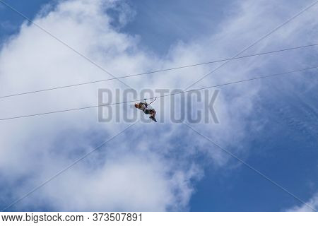 Monteverde, Costa Rica - August 26, 2019: young adventurous woman zip lining thru the forest. Monteverde, Costa Rica.