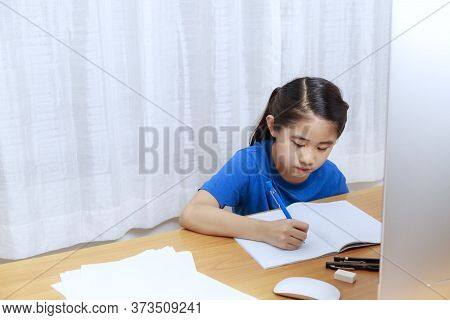 Asian Little Girl Is Studying Online Via The Internet  Sitting And Writing In  Living Room At Home.