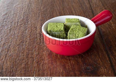 White Chocolate Fudge Heavily Coated With Fine Green Tea Powder In A Red Ceramic Dish. Brown Wooden
