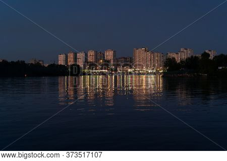 Evening At Dnipro River. Golden Lights Of Modern Buildings Reflect In Water. View On Poznyaki Distri