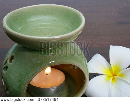 A Green Ceramic Aromatherapy Jar With A Candle Lit Up In Its Chamber. Heated Aromatherapy Oil Mixed
