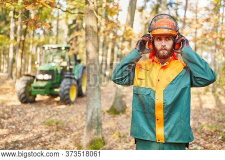 Forest worker with safety helmet and ear protection while forest work in the forest
