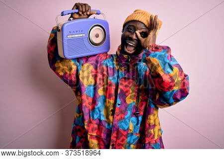 Young african american man listening to music holding portable vintage retro radio with happy face smiling doing ok sign with hand on eye looking through fingers