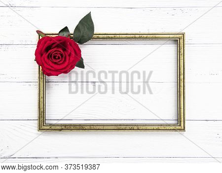 Gold Colored Vintage Wooden Frame And A Beutiful Solitary Red Rose.  Template Mock Up. Copy Space Fo