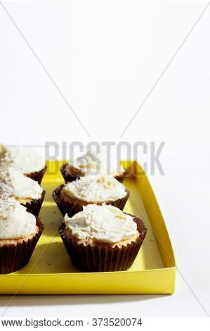 Vegan Vanilla Cupcake With Coconut Cream Frosting In Paper Cup On White Background.vertical Orientat