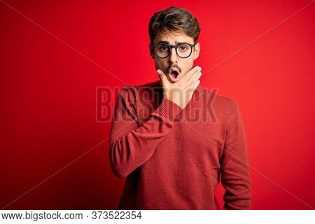 Young handsome man with beard wearing glasses and sweater standing over red background Looking fascinated with disbelief, surprise and amazed expression with hands on chin