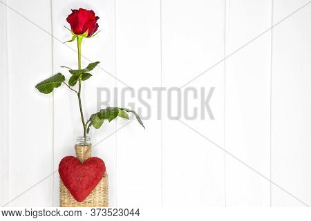 A Single Beautiflul Red Rose In A Bamboo Vase.   White Painted Teak Wood Background.