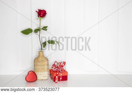 A Single Beautiflul Red Rose In A Bamboo Vase With A Red Gift Box And A Red  Paper Mache Heart.  Whi