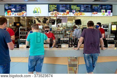Minsk, Belarus - June 11, 2020: Workers In Medical Masks Serve Customers At Mcdonald's Restaurant Du