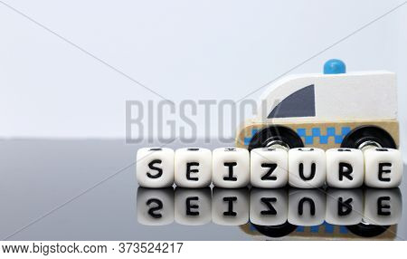 Image Of Letters Spelling A Word Seizure And A Model Ambulance On A Reflecting Background