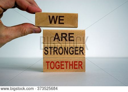 Male Hand Placing A Blocks With Word 'we' On Top Of A Blocks Tower. Text 'we Are Stronger Together'.