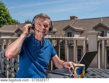 Senior Caucasian Man Working From Home During Coronavirus Epidemic Using Headset And Laptop To Commu