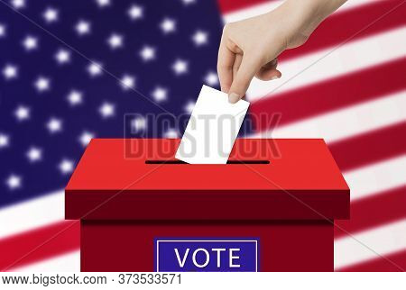 Us Elections Concept : Hand Holding And Putting Voting Paper In Ballot Voting Box With Usa Flag In B