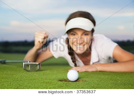 Happy woman golf player lying on green after successful shot. Focus on ball dropping into hole.