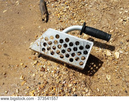 Metal Scoop Or Sieve In Sand Picking Up Shells And Rocks