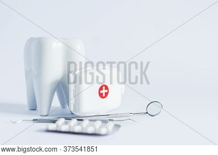 Model Of White Tooth, Medical Pills And Dentistry Tools On White Background.