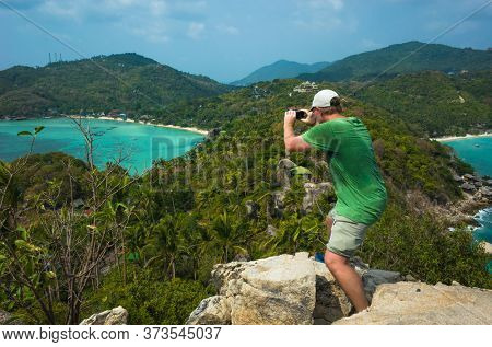 Tropical paradise island in Thailand, Koh Tao. Male tourist taking photo from John-Suwan Viewpoint