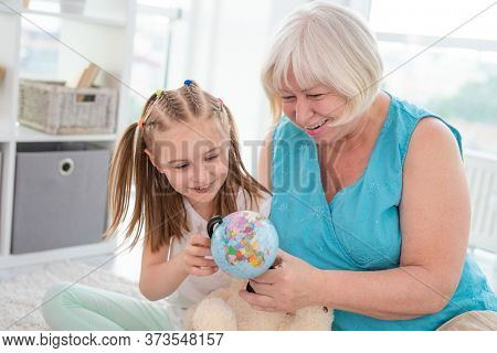 Happy granny showing globe to interested granddaughter in light room