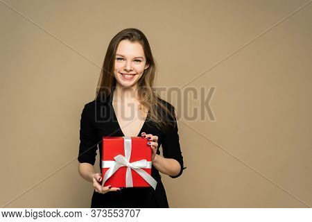 A Girl Is Holding A Red Present. A Girl Is Smiling. A Girl Has Got A Red Gift. Attractive Girl On Th