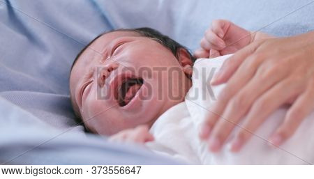 New born baby crying with hand comforting