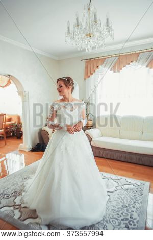 Girl In A White Dress At Home. Bride With Makeup. Wedding. Preparing The Bride For The Upcoming Wedd