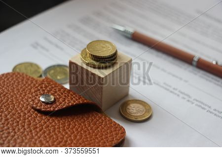 Brown Leather Wallet, Coins And Pen Put On Agreement. Business Invesment And Realestate Concept
