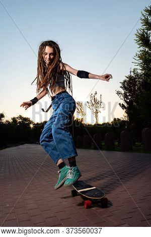 Slim Beautiful Girl With Dreadlocks Jumps On A Longboard In The Setting Sun