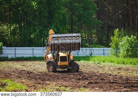 Clearing And Leveling A Private Land Plot. Yellow Excavator With A Large Wide Open Bucket