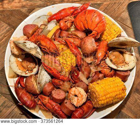 Cajun style seafood boil. Lobster, crawfish, shrimp, clams, potatoes, corn, and kielbasa sausages.