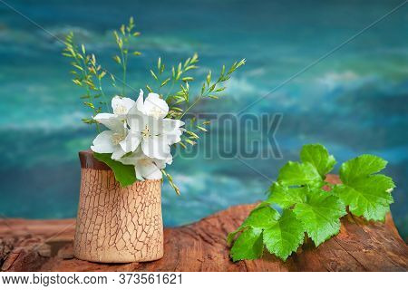 Bouquet Of White Flowers Of Wild Jasmine And Green Leaf On The Artistic Background. Rustic Still Lif