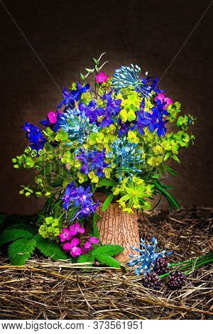 Still Life With Wildflowers In A Clay Vase On A Hay. Bouquet Of Yellow, Pink And Blue Wildflowers. R
