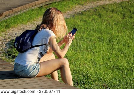 Slim Girl In Short Jeans Shorts With Backpack Sitting With Smartphone In A Summer Park. Concept Of O