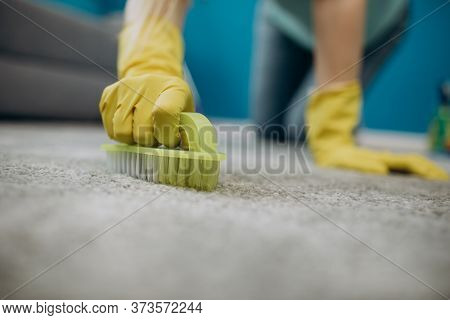 Close Up Of Housewife In Gloves Cleaning Carpet With Brush
